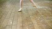 tüt : close up, in dancing hall, ballerina perform step pointe , She is standing on toes in pointe shoes elegantly , on an old wooden floor, in ballet class.