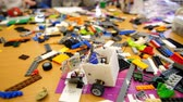 образовательный : on the table there are scattered a lot of details from the childrens designer, cubes, wires, boards, wheels,