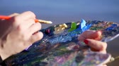 several : summer,outdoors, close-up of female hands of the artist and a palette with paints, the artist mixes paints with a brush on the palette. Stock Footage