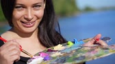 pár : summer,outdoors, portrait of a beautiful forty years old brunette woman artist, close-up of a palette with paints, the woman artist mixes paints with a brush on the palette.