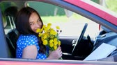 jediný květ : beautiful brunette woman sitting in the car, with a bouquet of yellow dandelions. smiling. summer Dostupné videozáznamy