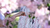 obra prima : close-up, female hand, painter, artist paints a picture of flowers in blooming spring apple orchard, she applies paints to canvas with special small spatula, holds palette with paints Stock Footage