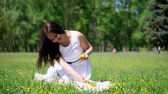 věnec : summer, beautiful brunette woman in white dress, sits on green lawn, grass, weaves a wreath of yellow dandelions, smiles Dostupné videozáznamy