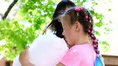 domingo : brunette woman, wearing sunglasses, with her daughter, girl of 8 years old, with blue pigtails, eating sweet cotton candy, candyfloss, laughing, having fun, in city park, in summer