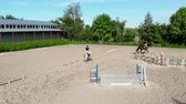 engel : view from above, aerial video shooting, training sand field, playground, riders, jockeys ride horses, perform various exercises with horses, next to barriers. summer, outdoors,