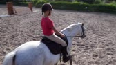 dressage : summer, outdoors, boy rider, jockey riding on thoroughbred beautiful white stallion, horse, on the training sand field, ground. boy learns to ride a horse in horse riding school.