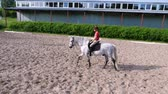 eyer : summer, outdoors, boy rider, jockey riding on thoroughbred beautiful white stallion, horse, on the training sand field, ground. boy learns to ride a horse in horse riding school.