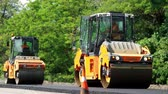 pressão : CHERKASSY REGION, UKRAINE - MAY 31, 2018: repair of a highway, Road construction works. roller compactor machine and asphalt finisher laying a new fresh asphalt pavement,