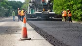 paver : CHERKASSY REGION, UKRAINE - MAY 31, 2018: repair of a highway, Road construction works. workers lay asphalt. There are lots of special equipment, machines for paving asphalt