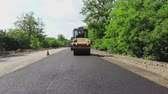 paver : repair of a highway, roller compactor machine and asphalt finisher laying a new fresh asphalt pavement, covering on one side of the traffic. Road construction works