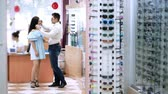 оптический : shop glasses, optics, beautiful married couple choose their own glasses, rims glasses. Happy couple trying on glasses in shop, Optical Store. health care concept