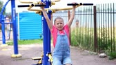 plac zabaw : smiling, happy eight year old girl engaged, doing exercises on outdoor exercise equipment, outdoors, in the park, summer, hot day during the holidays.