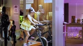 behind the wheel : cheerful attraction. The girl twists pedals of bicycle, holds the steering wheel with both hands. and next to, behind the glass on bike sits a skeleton and also turns the pedals of a bicycle. Stock Footage
