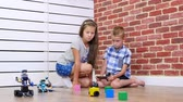 oktatói : seven-year-old boy and girl play electronic robots, cars, modern toys on the radio control. new technologies in the childrens gaming industry. little geniuses