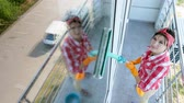 empregada : in the window glass is reflected smiling Caucasian Beautiful woman, in gloves, Cleaning, washing Window by special mop, enjoying her work. Cleaning service Stock Footage