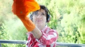 служащий : view through the window, smiling woman in headphones, in gloves, Cleaning Window by spraying Cleaning Products, using detergent and rag. listening to music, cleaning service Стоковые видеозаписи