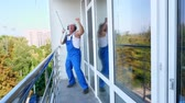 stereo : Caucasian attractive man, cleaning service worker, in blue overalls with headphones, having fun, dancing, playing on washing Windows mop guitar, happy and crazy