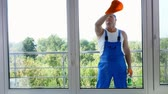 empregada : view through window, attractive male cleaning service worker, in blue overalls and in blaser, Cleaning Window by spraying Cleaning Products, using detergent, rag