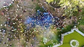 independence square : CHERKASY, UKRAINE - AUGUST 24, 2018 : aerial video with drone, Independence Day celebration, festival of colors, people throw up yellow and blue paints in sky, national flag