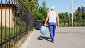 переработаны : back view, man is carrying a package of garbage in his hands, take out trash. summer hot day. ecology. separation of debris, cleanliness of the environment