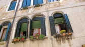 benátský : VENICE, ITALY - JULY 7, 2018: beautiful old architecture of Venice, a house with old green shutters and flowers on the windowsills, against the blue sky, on a hot summer day,