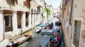 érckoporsó : VENICE, ITALY - JULY 7, 2018: narrow canal between the ancient houses of Venzia, hot summer day. Boat transportIng the coffin, decorated with red roses. funeral in Venice, Stock mozgókép