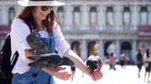 marco : Portrait of happy woman, tourist, holding pigeons, feeding, play with them, having fun on Piazza San Marco, St Marks Basilica, on a summer day