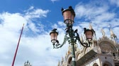 marco : Piazza San Marco, beautiful vintage lantern near the building of St Marks Basilica, many pigeons are sitting on the lantern. against the blue sky,