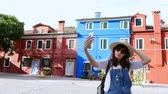 momentka : Burano Island with multicolor houses near Venice. tourist, young woman, girl in sun glasses, hat, backpack, makes selfie with smartphone against the background of houses, architectural structures of the island of Burano.