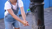 внешний : Crystal clear water flows from an old Public Iron Fountain , a well, kid girl washes her hands under a stream of water. close up Стоковые видеозаписи
