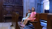 pew : OROPA, BIELLA, ITALY - JULY 7, 2018: children are sitting on a bench in a catholic old church, looking at wall paintings. Shrine of Oropa, Sanctuary, in the mountains near the city of Biella, Piedmont, Italy. Stock Footage