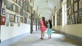 bilinen : OROPA, BIELLA, ITALY - JULY 7, 2018: two pretty kid girls, walk along long corridors, view pictures, photos on the walls. Shrine of Oropa, Sanctuary, in the mountains near the city of Biella, Piedmont, Italy.
