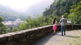 мадонна : OROPA, BIELLA, ITALY - JULY 7, 2018: beautiful couple man and woman walking in park in mountains, near Shrine of Oropa, Sanctuary, Sacro monte della beata Vergine, located in the mountains near the city of Biella, Piedmont, Italy.