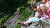 motýlek : two pretty girls, kids, sit on a ledge in the rock., a beautiful orange mountain butterfly whirls and flies over a childs leg in sandals. butterfly sits on the foot. summer hot day