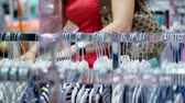 thrift : close-up, female hands sorted out many hangers with outfits. selection and purchase of clothes in the store. shopping. shopaholic. shopper looking through clothing on racks Stock Footage