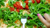 rúcula : close-up, big juicy, hot pizza with greens, arugula and cherry tomatoes. female hands cut pizza with a knife and fork Vídeos