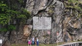 santuário : OROPA, BIELLA, ITALY - JULY 7, 2018: aero View of beautiful large inscription on rock near Shrine of Oropa, sanctuary located in mountains. Tourists walking in park in mountains,