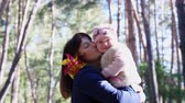pinwheel : CHERKASY, UKRAINE, OCTOBER 17, 2018: A small, pretty two-year-old girl holding a windmill in her hand and is hugging her mother, in an autumn park. warm autumn sunny day. Stock Footage