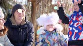 peruka : CHERKASY REGION, UKRAINE, DECEMBER 25, 2018: winter, frosty, snowy, sunny day. happy family, mother with small children throw up multi-colored tinsel and confetti, outdoors, having fun. Wideo