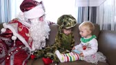 kolano : CHERKASY REGION, UKRAINE, DECEMBER 25, 2018: family new year, christmas. family with small children dressed in Christmas costumes. Santa Claus visits children. they have fun together, get presents