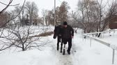 hipopótamo : winter, there is a young disabled man on the way. he has a prosthesis instead of his right leg. he leads a black thoroughbred horse. concept of rehabilitation of the disabled with animals. equestrian sports. Stock Footage