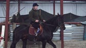 žokej : in special hangar, a young disabled man learns to ride a black, thoroughbred horse, hippotherapy. man has an artificial limb instead of his right leg. concept of rehabilitation of disabled with animals.
