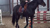 hipopótamo : in special hangar, a young disabled man learns to ride a black, thoroughbred horse, hippotherapy. man has an artificial limb instead of his right leg. concept of rehabilitation of disabled with animals.