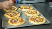 board : close-up, the process of cooking several mini pizza from yeast dough, with sausage and cheese. Chef sprinkles pizza with cheese. process of cooking bakery, in mess hall, resturant. Stock Footage