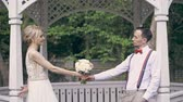 野球 : a young beautiful couple are standing in the gazebo, opposite each other and passing each other a wedding bouquet, fooling around, smiling. spring sunny day. wedding 動画素材