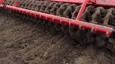 close-up, tractor cultivator cultivates, digs the soil. tractor plows the field. automated tiller for digging soil in farm into freshly plowed land. spring