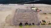 kucak : Aero, top view. Go-cart racing on circuit outdoors. There are safety barriers made of old wheels. Summer