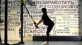 mide : CHERKASY, UKRAINE, NOVEMBER 20, 2019: TRX training. young pregnant athletic woman, with a large belly, in a black tight-fitting tracksuit, is doing exercises with trx fitness straps in the gym