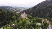 cavaleiro : aero. panoramic view of the ancient Bran castle on a hill , Dracula Castle, Transylvania, Brasov, Romania. at the foot of the castle there is a small town. summer day Stock Footage