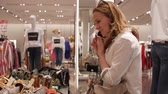 Girl talking on the phone in a clothing store 動画素材